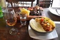 レストラン「マンダカル」で提供するカシャッサ、郷土料理のフェイジョアン(右手前)、牛干し肉焼き(奥)=ブラジル・グアルーリョスで2019年2月日、山本太一撮影
