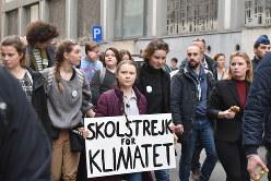 「気候のための学校ストライキ」と書かれたプラカードを手にデモの先頭を歩くグレタさん(中央)=ブリュッセルで2019年2月21日14時46分、八田浩輔撮影