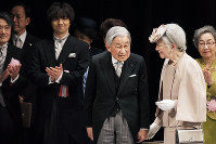 Japanese Emperor Akihito, center, and Empress Michiko, right, leave the stage after a ceremony to mark the 30th year of the Emperor's reign at the National Theater on Feb. 24, 2019, in Tokyo. (Nicolas Datiche/Pool Photo via AP)