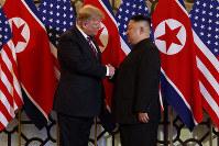 握手するトランプ米大統領(左)と金正恩朝鮮労働党委員長=2019年2月27日、AP