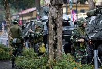金正恩朝鮮労働党委員長が滞在するホテル周辺で装甲車の近くに立って警戒する兵士ら=ベトナム・ハノイで2019年2月27日、AP