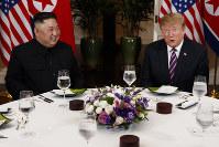 米朝首脳会談初日の夕食会で談笑する米国のトランプ大統領(右)と北朝鮮の金正恩朝鮮労働党委員長=2019年2月27日、AP