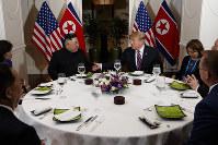 米朝首脳会談初日の夕食会で談笑する両国首脳ら=2019年2月27日、AP