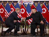 笑顔で再度握手するトランプ米大統領(左)と金正恩朝鮮労働党委員長=2019年2月27日、AP