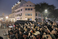 夕食会会場のホテル周辺に集まるメディア関係者や大勢の人々=2019年2月27日、AP