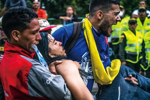 人道支援物資の国内持ち込みを図る人々と治安部隊が衝突、多くの負傷者が出た(2月23日)(Bloomberg)