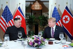 2月27日、夕食会で円卓に並んで座るトランプ米大統領(右)と金正恩朝鮮労働党委員長=ベトナムのハノイで(朝鮮中央通信=朝鮮通信)