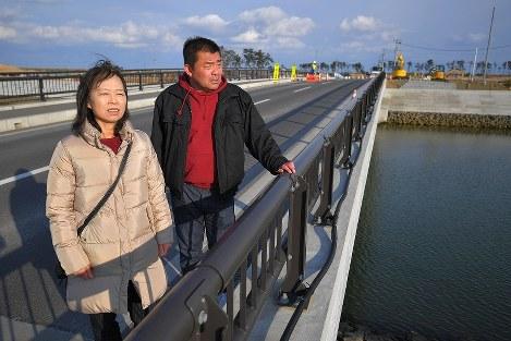 架け替えられた北釜橋を訪れ、震災時の状況を語る高橋愛子さん(左)と森浩利さん。右奥は現在も更地が広がる北釜地区=宮城県名取市で2019年2月11日、手塚耕一郎撮影