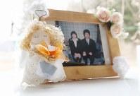 写真立てに付けられた天使。その天使が持つのは、震災で大勢の人が犠牲となった市民会館のタイルだ。小松満喜子さん(56)が作り、同級生の戸羽初枝さん(57)に贈った。市職員だった戸羽さんの長男究さん(当時24歳)と杏さん(同23歳)は市民会館付近で波に飲まれた。小松さんも母(同72歳)を震災で亡くした。小松さんは「市民会館はたくさん思い出があった場所。みんなでこの悲しみと向き合いたい」。戸羽さんは「手元に何か残したいと持ち帰ったタイルが、こんな形になってありがたかった」。2人の写真を入れ、そばにいられるようにと居間に飾っている=岩手県陸前高田市で2019年2月、小川昌宏撮影