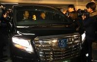 弁護士事務所で、日産前会長のカルロス・ゴーン被告(中央)が乗った車を取り囲む報道陣ら=東京都千代田区で2019年3月6日午後8時15分、宮武祐希撮影