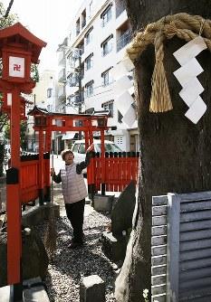歩道の中でしめ縄を付けて祭られるエノキ。古くから住むの地元住民たちが維持管理を続けている=大阪市北区長柄中2で、小出洋平撮影