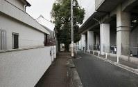 住宅と鉄道の高架に挟まれるように立つクスノキ=大阪市住吉区東粉浜2で、小出洋平撮影