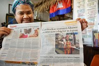 自身の記事が掲載されたカンボジアの英字紙を開く池田スロスさん=福岡市博多区吉塚で2019年2月1日午後3時44分、佐野格撮影