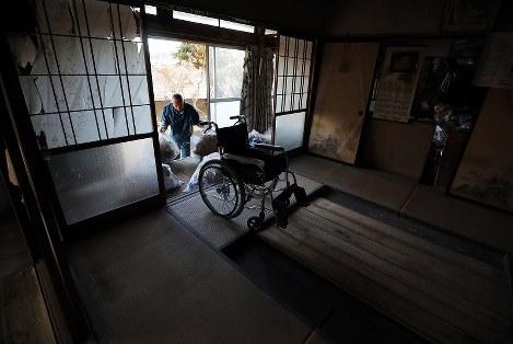 解体に備え、母トミノさん(享年89歳)の車いすが残された自宅を片付ける居村久男さん(66)。トミノさんは2年前、新潟県の避難先で亡くなった。父(92)は神奈川県に避難し古里に戻る見通しは立っていないが、今も自宅の解体を拒んでいるという=福島県浪江町で2019年2月1日午後2時56分、喜屋武真之介撮影