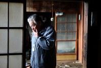 荒れ放題になっている築90年の自宅でたばこを吸う斉藤宗一さん(69)。斉藤家が双葉町に住み始めたのは約600年前で、宗一さんで16代目になるという。原発事故前までは親から孫まで4世代で暮らしていたが、今は離ればなれだ。地区全体が中間貯蔵施設予定地で、帰ってくるたびに変わる古里の景色に「寂しくなる」とつぶやく。まだ国との契約は結んでおらず、「最後の一人になったらサインするかな」=福島県双葉町で2019年1月24日、喜屋武真之介撮影