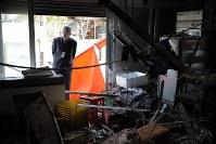 営んでいた食料品店の中を見つめる中田寛さん(63)。地震で屋根瓦がずれて雨漏りし、今では天井に大きな穴が空く。食料品をかぎつけた野生動物がシャッターをこじ開けて入り込み、店内は手が付けられないほど荒らされた。「初めて帰ってきたときは涙が出そうだった。今はもうあきらめた」。解体はまもなく始まる予定だ=福島県富岡町で2019年1月20日、喜屋武真之介撮影