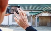 解体が始まる前日のJR夜ノ森駅を訪れ、写真を撮る中田寛さん(63)。生まれも育ちも富岡町で、食料品店を営んでいた我が家は駅から数分の場所にある。駅の隣の木材置き場は子どものころの遊び場。町外の高校に入学してからは、毎日のように駅の改札を通った。同町のシンボルでもある駅周辺のツツジの整備は、近隣住民にとって年に1度の大仕事だった。「愛着はある。けど、しょうがない」=福島県富岡町で2019年1月20日、喜屋武真之介撮影