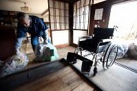 解体に備え、母トミノさん(享年89歳)の車いすが残された自宅を片付ける居村久男さん(66)。トミノさんは2年前、新潟県の避難先で亡くなった。父(92)は神奈川県に避難し古里に戻る見通しは立っていないが、今も自宅の解体を拒んでいるという=福島県浪江町で2019年2月1日、喜屋武真之介撮影