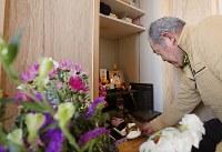 災害公営住宅のクローゼットに作った仮の仏壇に、ケーキを供える佐藤信行さん。この日は妻才子さんとの48回目の結婚記念日だった=宮城県気仙沼市で2019年3月8日、小川昌宏撮影
