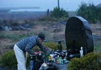 2015年12月の月命日。夜明け前、佐藤信行さんは集落の犠牲者93人の名前が刻まれた慰霊碑に、真っ赤なイチゴを供えた。慰霊碑には、母しなをさん(当時87歳)と、妻才子さん(当時60歳)の名前もあった。いっしょにイチゴ農家を営んできた=宮城県気仙沼市で2015年12月11日、小川昌宏撮影