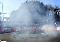 多くの観衆の前で、白煙を上げながら豪快にターンを決めるF1マシン=東京都港区で2019年3月9日午後2時34分、藤井太郎撮影
