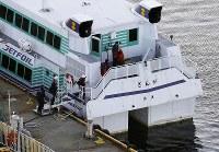 海洋生物とみられる物体と衝突した高速船を調べる海上保安官ら=新潟県佐渡市で2019年3月9日午後5時12分、本社ヘリから