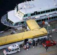海洋生物とみられる物体と衝突した高速船からけが人を運ぶ消防隊員ら=新潟県佐渡市で2019年3月9日午後5時17分、本社ヘリから