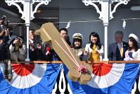 琵琶湖に「黄金の鍵」を投じる岸井ゆきのさん(中央)ら=大津市の琵琶湖上で2019年3月9日午前10時26分、成松秋穂撮影