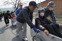 避難訓練で要救護者役の住民をリヤカーで運ぶなどして高台を目指す安渡地区の住民たち。同地区では津波で約190人の犠牲者が出た。毎年地域で避難訓練を実施し、黙とうを捧げている=岩手県大槌町で2019年3月10日午後1時28分、和田大典撮影