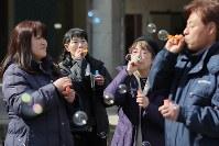 旧大川小学校を訪れ、亡くなった子どもたちの冥福を祈ってシャボン玉を作る早坂由里子さん(左から2人目)ら=宮城県石巻市で2019年3月10日午後0時57分、喜屋武真之介撮影