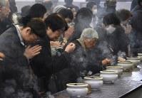一晩で推定約10万人が犠牲になったとされる東京大空襲から74年となった10日、遺骨が納められている東京都慰霊堂で焼香する人たち=東京都墨田区で2019年3月10日午前11時44分、丸山博撮影