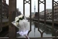 墨田区の菊川橋の欄干に供えられた花束。奥は東京スカイツリー。この川に入って奇跡的に生き延びたという女性(93)が供えた。「あの日はどこも遺体だらけだった。いまでも思い出したくない」と話していた=東京都墨田区で2019年3月10日午後3時12分、丸山博撮影