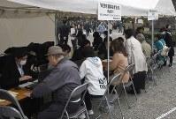 東京都慰霊堂を訪れ、犠牲者名簿について問い合わせる人たち=東京都墨田区で2019年3月10日午後0時1分、丸山博撮影