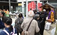 東京大空襲の遺族らの寄付で建てた「夢(ゆめ)違之(たがえ)地蔵尊」に向かって手を合わせる人たち。付近では約3000人が犠牲になったとされる。毎年3月10日に慰霊法要を行っているが、遺族の高齢化で参加者は年々減っているという=東京都墨田区で2019年3月10日午後2時29分、丸山博撮影