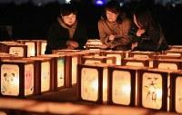 復興祈念公園「千年希望の丘」で行われた追悼行事で灯籠の灯火を見つめる参加者たち=宮城県岩沼市で2019年3月10日午後6時26分、玉城達郎撮影