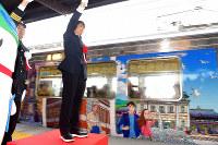 Illustrator Seizo Watase, right, gives a green light signal for a train decorated with his illustrations to depart from JR Mojiko Station in Kitakyushu's Moji Ward on March 10, 2019. (Mainichi/Takashi Kamiiriki)