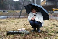 Nao Miura puts sweets on a stone at the site of her house in the town of Minamisanriku, Miyagi Prefecture, on March 11, 2019. Her then-3-year-old daughter Yu and her paternal grandparents were victims of tsunami following the 2011 Great East Japan Earthquake and remain missing. (Mainichi/Shinnosuke Kyan)