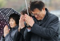 Makoto Inoue, front, puts his hands together with his family in front of the site of the Minamisanriku town's disaster prevention office on March 11, 2019. His then-23-year-old son Tsubasa, who was in the building, was killed by tsunami following the 2011 Great East Japan Earthquake. (Mainichi/Shinnosuke Kyan)