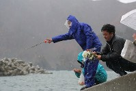 People throw flowers into the sea for victims of the 2011 Great East Japan Earthquake in the town of Yamada, Iwate Prefecture, on March 11, 2019. (Mainichi/Daisuke Wada)