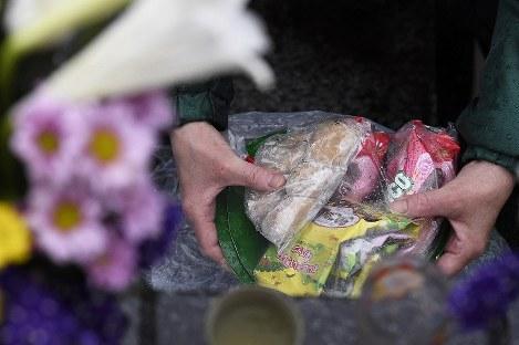 当時、2歳と3歳だった孫2人を津波で失った女性(60代)が墓前に供えた菓子。「(生きていれば)もうすぐ中学生になるのにね」と思いながらも、今でも子ども向けのお菓子を買って墓参りに訪れるという=岩手県大槌町で2019年3月11日午前6時51分、渡部直樹撮影