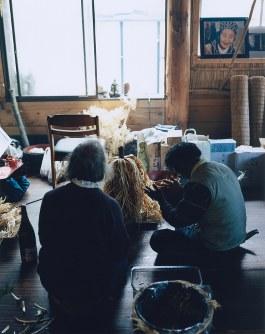 カムイノミ(神への祈り)。右奥には唇の周りにシヌイェ(いれずみ)を施した女性の写真が掲げられている。新ひだか町静内で2013年5月=「AINU」から(c)HIROSHI IKEDA