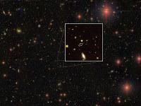 130.5億光年先にある巨大ブラックホール(矢印の先の赤い天体)=国立天文台提供