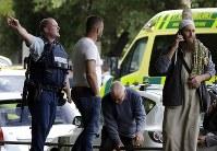 クライストチャーチのモスクの外で人々に避難を促す警官=AP共同