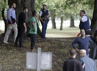 発砲事件の後、モスクの外で人々を遠ざけようと誘導する警官=ニュージーランド・クライストチャーチで2019年3月15日、AP
