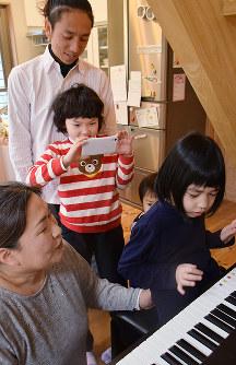 音楽が好きというドラベ症候群の佐々木寿姫さん(右)と母親の千恵さん。奥は貞本実音さんと父親の建太さん=京都市伏見区で、南陽子撮影