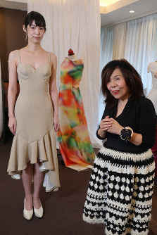 Fashion designer Ema Rie, right, stands next to one of the dresses she designed in cooperation with AI, modeled by Momoko, in Tokyo's Minato Ward on Feb. 15, 2019. (Mainichi/Etsuko Nagayama)
