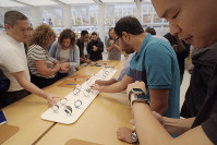 In this Sept. 21, 2018 file photo customers look at Apple Watches at an Apple store in New York. (AP Photo/Patrick Sison, File)