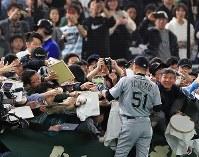 The Seattle Mariners' Ichiro Suzuki signs autographs ahead of an exhibition game versus the Yomiuri Giants at the Tokyo Dome, on March 17, 2019. (Mainichi/Tatsuro Tamaki)