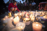 Candles are placed to commemorate victims of the March 15 shooting, outside the Al Noor mosque in Christchurch, New Zealand, on March 18, 2019. (AP Photo/Vincent Thian)