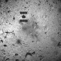 This Feb. 22, 2019 photo released by the Japan Aerospace Exploration Agency (JAXA) shows the shadow, center above, of the Hayabusa2 spacecraft after its successful touchdown on the asteroid Ryugu. (JAXA via AP)